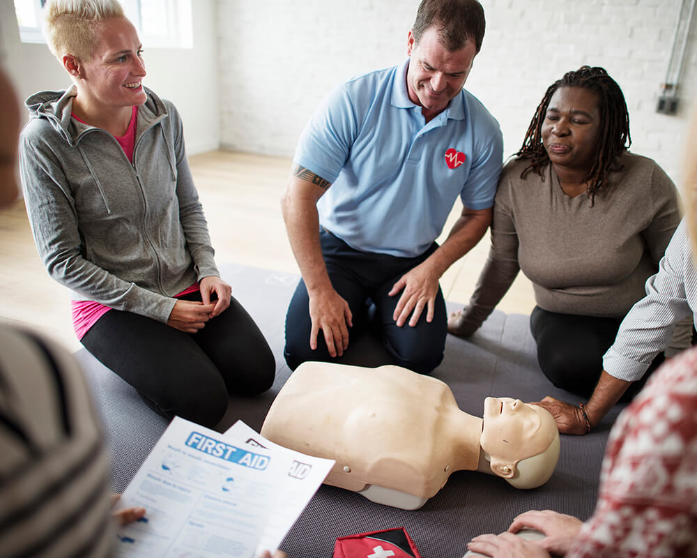 adults practicing CPR with instructor