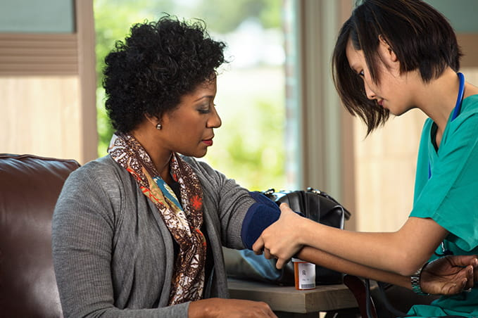 woman taking blood pressure on another woman