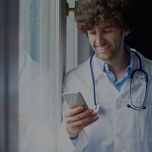 male medical worker looking at his smartphone