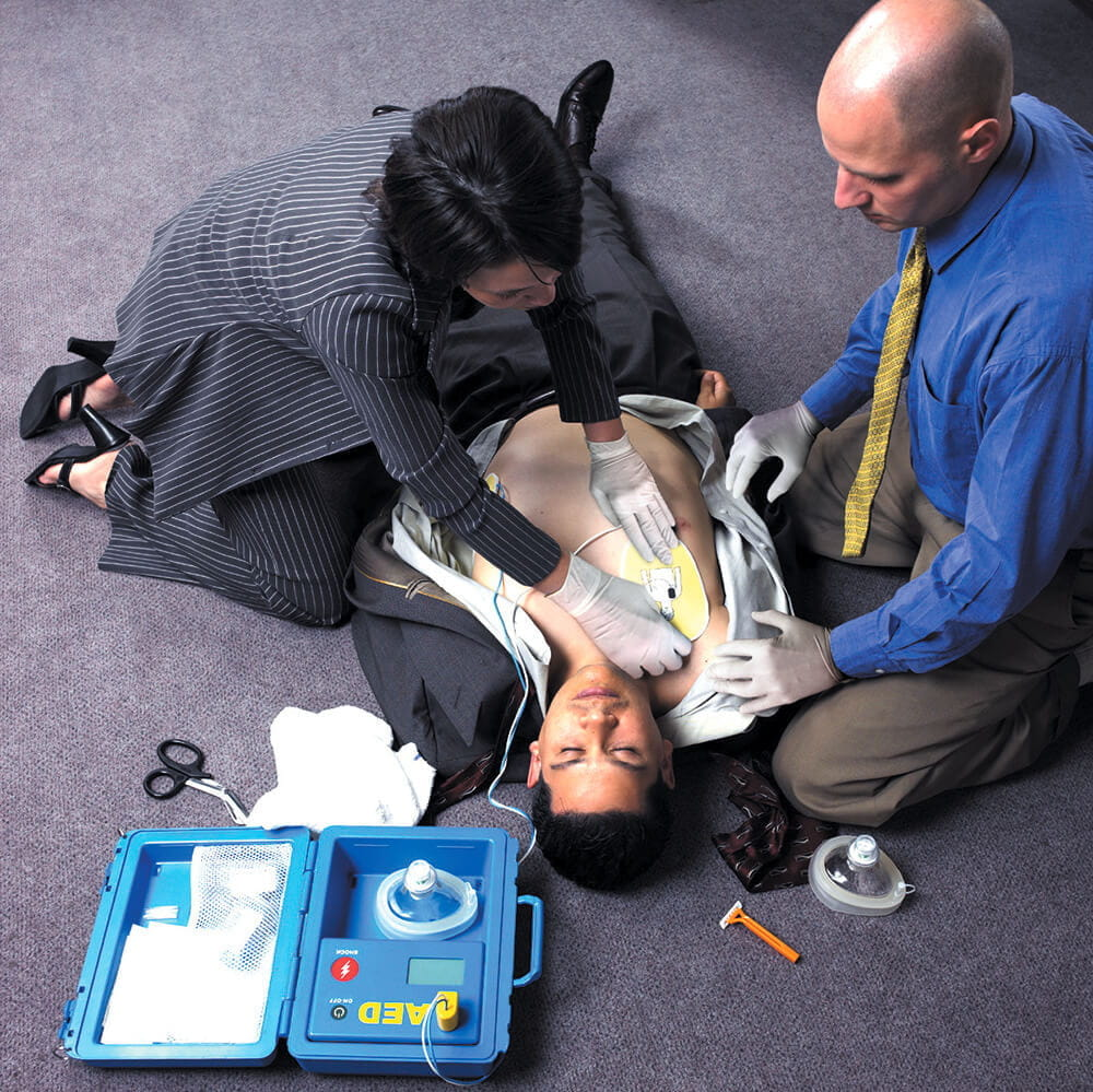 business woman using AED on man on office floor