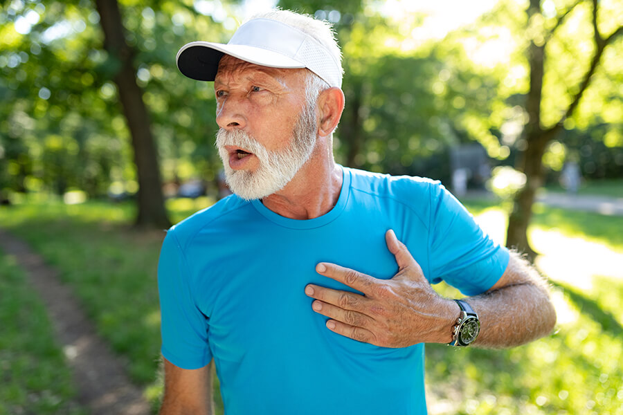 senior man with chest pain in a park