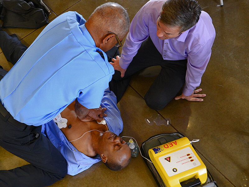 two men performing CPR with AED on unconscious man on the floor