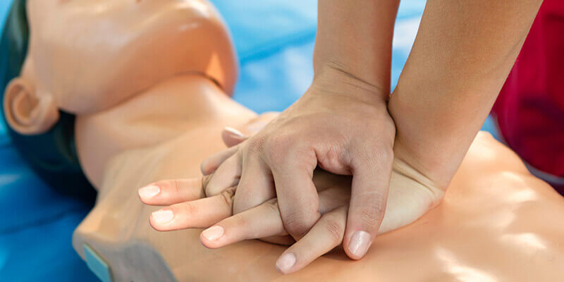 hands performing chest compressions on manikin