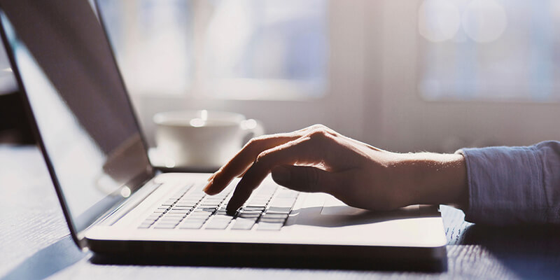 hand typing on laptop indoors