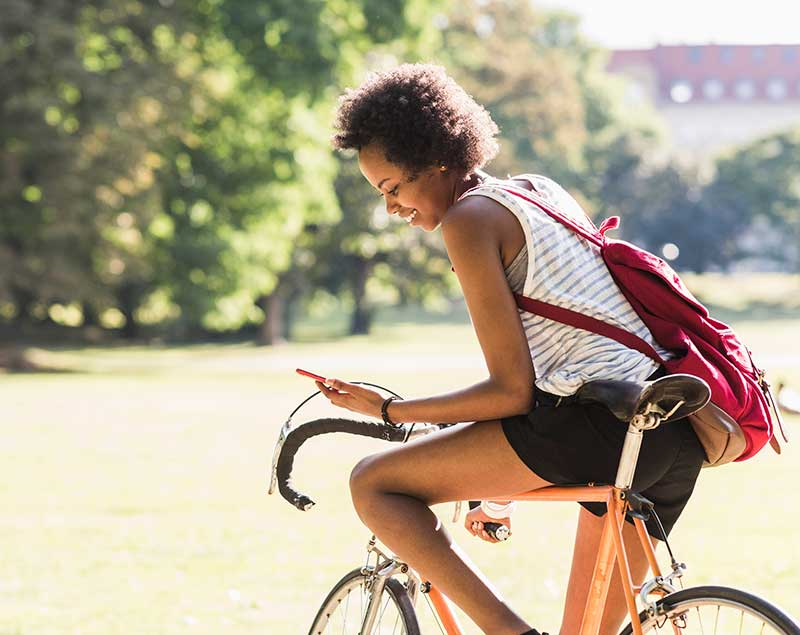 young woman on bicycle reading phone