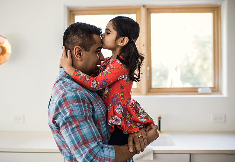 daughter kissing fathers forehead at home